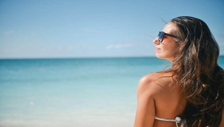 Frau am Strand schützt Augen
